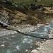 The somewhat wobbly suspension bridge to cross the small river Ava da Curtegns.