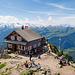 Gasthaus auf dem Grossen Mythen. Es tummeln sich viele Leute auf dem Gipfel.