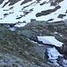 <b>Alle 6:45 mi trovo già in fondo al lago, al ponticello sul torrente Sella (2306 m). La pista lambisce una baracca militare e prosegue con ampi tornanti, ricoperti da nevai gelati.</b>