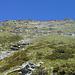Il percorso di salita indicativo visto dai pressi dell'ometto di pietra di quota 1960 m. Rispetto alla fotografia, dal vivo la rampa-diedro che conduce alla cresta est è sempre ben distinguibile.