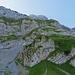 Der Anfang der Route geht über das Grasband zwischen den Felsen hinauf.