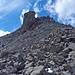 Aufstieg über Blockgestein. Zwischen den beiden in der Höhe sichtbaren Felsbastionen geht man durch. Dort hat es im Boden grosse, tiefe Löcher!