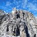 Gipfelaufbau der Elferspitze. Vom Steig (links) quert man zunächst über eine mit einem Drahtseil gesicherte Steilstufe nach rechts. Danach steigt man durch einen kaminartigen engen Spalt (einige Bügel) senkrecht nach oben zum Gipfelkreuz.