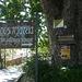 Am Dorfplatz. Rundes Hinweisschild l für den Abstieg zu Kala Nera am Baum