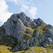 """Brunnistöckli im Überblick ca. von der Brunnihütte aus. Der Klettersteig Brunnistöckli verläuft in etwa dem Grat am Horizont auf der rechten Seite entlang. In Originalgrösse sieht man ein paar Personen auf der Route. Der Zittergrat Klettersteig verläuft im kompakten Wandteil knapp links vom """"Gipfelkreuz"""". Der Wegpunkt """"Zittergrat Klettersteig Brunni"""" markiert hier den Einstieg zum Zittergrat. Den Wegpunkt """"Brunnistöckli Klettersteig"""" habe ich misbraucht um einen Punkt vom ersten Drittel der Wegstrecke zu markieren, wo sich gerade ein Klettersteiggeher befindet. Von der Höhenangabe her sollte er vermutlich beim Kreuz oder sogar beim (hier nicht sichtbaren) Ausstieg platziert werden."""