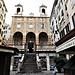 """Chiesa di San Pietro in Banchi. L'attuale chiesa, della seconda metà del '500, fu progettata dagli architetti Andrea Ceresola detto il Vannone e da Giovanni Ponzello che si ispirarono alla basilica dell'Assunta a Carignano.<br />La sopraelevazione della chiesa permise la realizzazione di negozi sottostanti la cui vendita contribuì a finanziare l'opera.<br />Molte delle botteghe erano occupate dai """"banchi"""" dei cambiavalute, cioè da grandi lastre di marmo su cui si svolgevano le transazioni, da cui la denominazione di San Pietro in Banchi. Da notare che quando uno dei """"banchi"""" falliva la lastra marmorea veniva spezzata, questo ha dato origine al vocabolo """"bancarotta""""."""