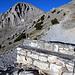 Im Aufstieg (T2) zum Skala (2866m). Eine Steinbank lädt zu einer kleinen Rast in der Morgensonne ein. Hier zweigen auch mehrere Wege zu den umliegenden Gipfeln und Hütten ab.