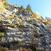 Bei genauer Betrachtung sieht man die Eisenstangen und die weiss-blau-weissen Markierungen, die durch die Felswand zum Sitzstein führen.