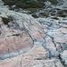 Im Abstieg zwischen Lac du Cinto und Refuge de l'Erco - Über mehrfarbige, glatt geschliffene Felsplatten. Hier auf einer Höhe von ca. 2.000 m. Auch ein Steinmännchen ist mal wieder zu erahnen.