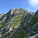 Entlang dem S-Grat zur SW-Flanke (sichtbare Pfadspuren): oben links der Gipfel, rechts die Gendarmen im E-Grat