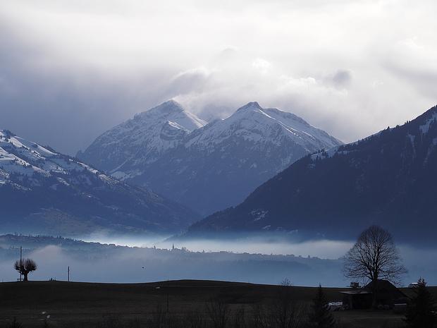 Dunstige Thunersee-Gegend. Vom Süden her drücken die Wolken über die Berner Alpen.