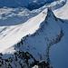 Tiefblick vom Gipfel dem Südgrat entlang zum Guspissattel, wo die beiden anderen Tourengeher ihre Ski deponiert haben. Rechts davon der Steilhang.