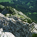 Im Tiefblick vom Gipfel auf den südseitige Gipfelanstieg von oben. Der anscheinend UV-strahlungsresistente, einheimische Bergvagabunt hat gerade balancierend und stolpernd die erste Schlüsselstelle dieser Route (ca. 10m hinter ihm) hinter sich gebracht und überschreitet gerade mutig die nächste.