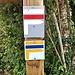 Französische Wegmarkierungen. Die Weiss/Rote führt einen am französischen Ufer entlang. Die geknickte Markierung zeigt einen Abbieger nach rechts an. Bei Geradeaus sind nur jeweils die beiden oberen Streifen zu sehen.