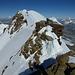 Zwischen E Vorgipfel und Liskamm W-Gipfel: vorne leicht zu überkletternde Felsen, links die Felsstufe, wo man etwas beherzter zupacken muss (Schlüsselstelle, III). Hinten links der Mont Blanc, links die Dent Blanche