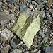 Ein grüner Brocken inmitten andersfarbigen Steinen