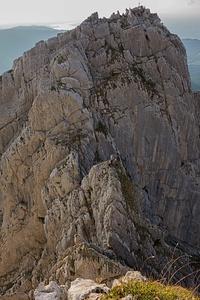 Der Abstieg von oben: Im Hintergrund der Bockmattligipfel (großer Turm) und die 50 m Abkletterflanke in Bildmitte. Drei Kletterer am Gipfelblock des zweiten Gendarmen (wo man eigentlich nicht Stand machen sollte, sondern gleich 5 m weiter gehen zum Abseilring. Ein Kletterer mit grünem Rucksack machts richtig und wird von Kameraden (in gelb) am Abseilring abgelassen. Weiter im Vordergrund der dritte Gendarm (brüchiger, nach rechts abfallender Grasgrat; an dessen rechten Ende ist die Abseilschlinge). Danach gehts nochmal runter und von dieser letzten Sxcharte dann 70 m hoch zum Standpunkt des Fotografen.