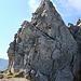 Die Leiter führt auf einen kleinen Felskopf, von wo aus man leicht ausgesetzt zum nächsten Zacken (rechts am Bildrand) quert.