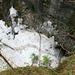 Unvermittelt ist es wieder Winter. Blick hinunter zum Eingang Glacière de Monlési, wo noch haufenweise Schnee liegt