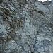 Rote Pfeile und Steinmänner weisen den Weg durch die Felsbastion von P. 2619, hier das unterste Diagonalband