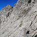 hier bei diesem Pfeil geht eine schwache Spur geradeaus weiter, es geht aber nach rechts den Felsen hinauf.