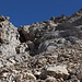 Im Abstieg von der Vetta Orientale - Rückblick auf die kurze, praktisch senkrechte Felspassage. Diese ist klettersteigmäßig mit Stahlseil gesichert. Bei genauem Hinsehen sind dort auch zwei Berggänger zu erkennen.