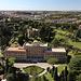 """Petersdom (Basilica di San Pietro in Vaticano) - Ausblick von der Kuppel in etwa westliche Richtung. Unten ist der Governatoratspalast (Palazzo del Governatorato) zu sehen, dahinter das Päpstliche Äthiopische Kolleg (Pontificio Collegio Etiopico). Hinten sind auch zwei vatikanische Türme zu erahnen: der Johannesturm, Torre San Giovanni (links) und der Turm mit einem Sendemast (aka """"Torre Leonina"""", rechts)."""