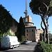 """Unterwegs in den Vatikanischen Gärten (Giardini Vaticani) - Blick entlang eines verbliebenen Abschnittes der Leoninischen Mauer (Mura Leonine), einer mittelalterlichen Befestigungsanlage, die im Bereich der Gebäude nach Osten (rechts) schwenkt. Hinten ist der """"Torre Leonina"""" teilweise zu erahnen. Zwischenzeitlich (Anfang 20. Jh.) befand sich dort offenbar das Observatorium (heute in Castell Gandolfo), aktuell ist die Verwaltung von Radio Vatikan ansässig. Gemäß topografischer Karte des Istituto Geografico Militare (1:25.000) ist die höchste Stelle unmittelbar südöstlich (rechts) der Gebäude eingetragen. Eine weitere, oft favorisierte Stelle befindet nördlich davon (dahinter)."""