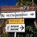 <b>Di fronte al Monumento dei Caduti osservo i segnavia per il Monte Bisbino. Sono un mix di cartelli segnaletici e pubblicitari che indicano tutti la medesima direzione, lungo la Via Per il Bisbino.<br />Da questo punto inizia pure, alla destra, il 'Sentèe di Sort', un'antica via di collegamento tra Rovenna e Moltrasio, riaperta nel 1993 dai volontari dell'Associazione Pro Rovenna con la collaborazione della sezione CAI di Moltrasio. Anticamente era ritenuto un percorso impervio, esposto e pericoloso, da cui il nome di sentiero della sorte. </b>