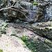 hinten am Felsen der blaue Pfeil mit dem M, verkehrte Richtung. Der Felsen ist überhängend, nicht leicht zu queren, denn es geht steil abwärts und nass ist es auch noch.
