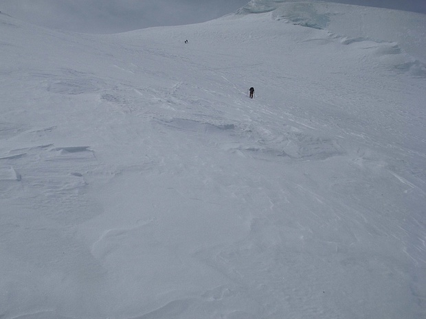 Oben sieht man eine Zweierseilschaft, die (nur) mit Bergschuhen ausgerüstet nur sehr langsam aufsteigt.