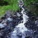 von den steilen Seitenwänden fließt überall Wasser über brüchiges Gestein