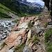 Schon bald nach Beginn ist der Hüttenweg mit Ketten gesichert. Früher verief hier der Weg im Schotter des Hinterrheins bis der Fluss nach Unwettern sein Bachbett änderte.