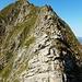 Zum Gipfel hin wird es dann spürbar felsiger. Ein Aufschwung wird rechts umgangen, es wird schmal und ausgesetzt, und am Gipfel muss nochmal geklettert werden.