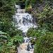 Hier mache ich wieder meinen gewagten Spreizschritt auf die Felsen im Bachbett unterhalb des Wasserfalls. So bekommt man die Flucht mit den drei Fallstufen hintereinander am besten drauf.<br />Aber natürlich am aller-interessantesten: die enormen Wassermengen, die an diesem Oktobermorgen herunterrauschen! Der Wasserfall und das darunter folgende Bachbett haben sich in ein tosendes Drama verwandelt.<br />Auch dieser Besuch hat sich definitv gelohnt.