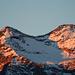 Das Croslina-Gletscherchen noch im Schatten, der Gipfelsteinmann blickt in den Sonnenaufgang