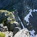 Vor dem Kreuz der Ausstieg aus der Abstiegsrinne. Im Hintergrund die schneebedeckte Boccetta d'Erbea.