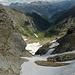 Abstieg durch das noch gut mit Trittfirn gefüllte Piz de Cressim NNW-Couloir: unten der weite Kessel von Cressim und das Val d'Arbola. Über die Gipfel des Hinterrheins und oberen Misox schiebt der Nordföhn immer wieder neue Wolken nach Süden