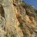 Die Beato Bottarga führt durch roten Fels links am roten Überhang in Bildmitte vorbei bis unter das grosse schwarze Loch. Im grauen Wandteil links führt Spalmabile Piccante rechts des Überhangs am linken Bildrand hoch.