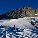 In einem langgezogenen Bogen geht es nun ganz links beim Nordostgrat hinter den Gletscherabbruch und hinter diesem zum Schneecouloire welches auf der rechten Bildseite bis zum Grat hinauf reicht.
