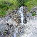 Erfrischender Wasserfall am Weg