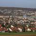 Aussicht bei Schlossguet auf den Dorfrand Pfeffingen (389m). Die vielen Häuser am Hang in der Ferne gehören zu Reinach (304m).