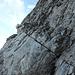 """Die überhängende Stufe links vom Kamin erwies sich für mich als """"echtes Boulderproblem"""" (IV), das sich aber mit einem Camalot im markanten Schrägriss und einem Rock rechts darüber genügend absichern liess. Ab der im Bild noch hängenden Schlinge nahmen die Schwierigkeiten dann deutlich ab"""