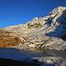 Rifugio Bertacchi (2175m): Nachmittagsstimmung bei der Hütte mit dem schon teilweise gefrorenen Lago di Emet (2144m) und dem morgigen Gipfelziel Piz Timun / Pizzo d'Emet (3212m).