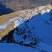 Piz Curvér (2971,8m): Tiefblick vom Gipfel über den 200m hohen Nordwestgrat welcher auch während des Abstiegs immer noch im Schatten lag. Dank gutem Trittschnee oder aperen stellen war der Abstieg eine rasche Angelegenheit ohne jegliche Schwierigkeiten. Im weiteren Gratverlauf stehen Curvér Pintg da Neaza (2720,8m) und der Piz Neaza (2626,0m).
