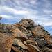 Bei dieser Holzstange erreicht man den Gipfelgrat