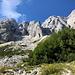 Im Aufstieg Okrešlj und Savinjsko sedlo - Seitenblick, u. a. zu Turska gora und einige Rinke-Gipfeln (rechts). Etwas rechts der Bildmitte dürfte auch der Turski žleb zu erahnen sein, der Weg dorthin ist soeben von unserem abgebogen und führt am Waldstück vorbei.