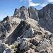"""Velika (Koroška) Baba - Ausblick über den zuvor bestiegenen Ledinski vrh hinweg. Dahinter ragen die Rinke auf, rechts ist die Skuta zu sehen. Nun begeben wir uns auf den Rückweg: Nach dem Abstieg von der Velika Baba geht's anschließend hinauf zum Sattel beim Grenzstein XXII/268 (zwischen Storžek und Ledinski vrh). Dass der Pfad steil durch Schutt führt, kann man in """"Originalgröße"""" erahnen."""