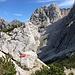 """Im Abstieg von der Velika (Koroška) Baba - Hier zweigt der Klettersteig (""""nach rechts unten"""", verdeckt) in/aus Richtung Kranjska koča ab. Wir drängeln uns am großen Felsblock vorbei und steigen noch ein Stück ab, bevor gleich der Aufstieg hinauf zum Sattel beim Grenzstein XXII/268 beginnt. Der Pfad durch den steilen Schutthang ist hinten zu erahnen."""