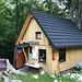 """Okrešlj - Da die eigentliche Hütte 2019 durch einen Brand zerstört wurde, dient diese Holzhäuschen momenatn als """"Frischaufov dom na Okrešlju"""". Neben Getränken und dergleichen gibt's auch T-Shirts oder Tücher, mit deren Kauf der Wiederaufbau der Hütte unterstützt wird."""
